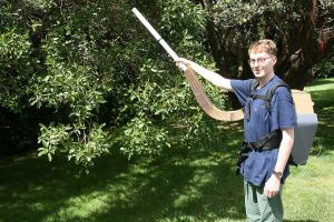 Industrial design student Liam Brankin demonstrates how his Swarmstorm backpack would work recollecting bee swarms