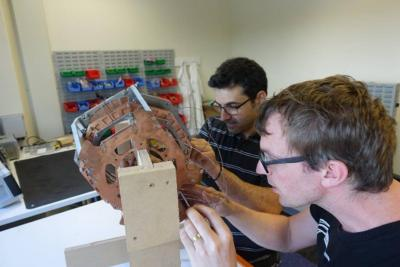 Ben Parkinson (right) and Konstantinos Bouloukakis working on a helmet-style MRI magnet (half-scale version), developed as part of the KiwiNet Emerging Innovator Programme