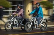 Ethan Ralston (left) and his father Bob Ralston ride the latest street-legal version of their Ubco electric motorcycle through downtown Eugene recently.
